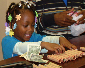 Photo - Wealth Building - Little Girl Counting Rolled Up Coins at Teller Desk